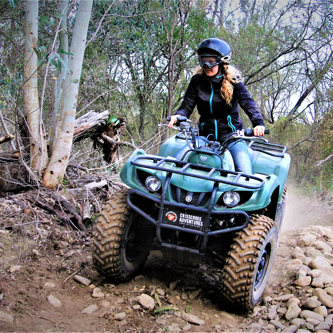 Adventurous woman riding a quad bike on a rough trail through the bush.